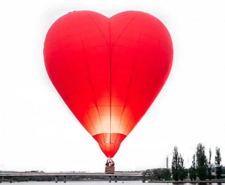 Hear shape red hot air baloon flying over a landscape