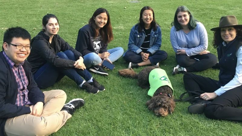 Roz Rimes with her dog Flash and students at the University of Melbourne.
