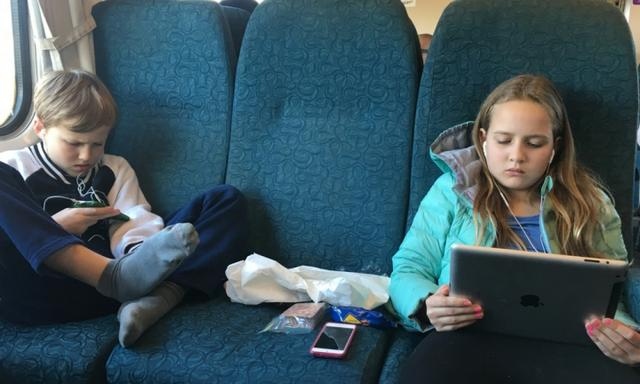 The kids on the train, just as most kids are - comfortable and connected! Image: supplied.