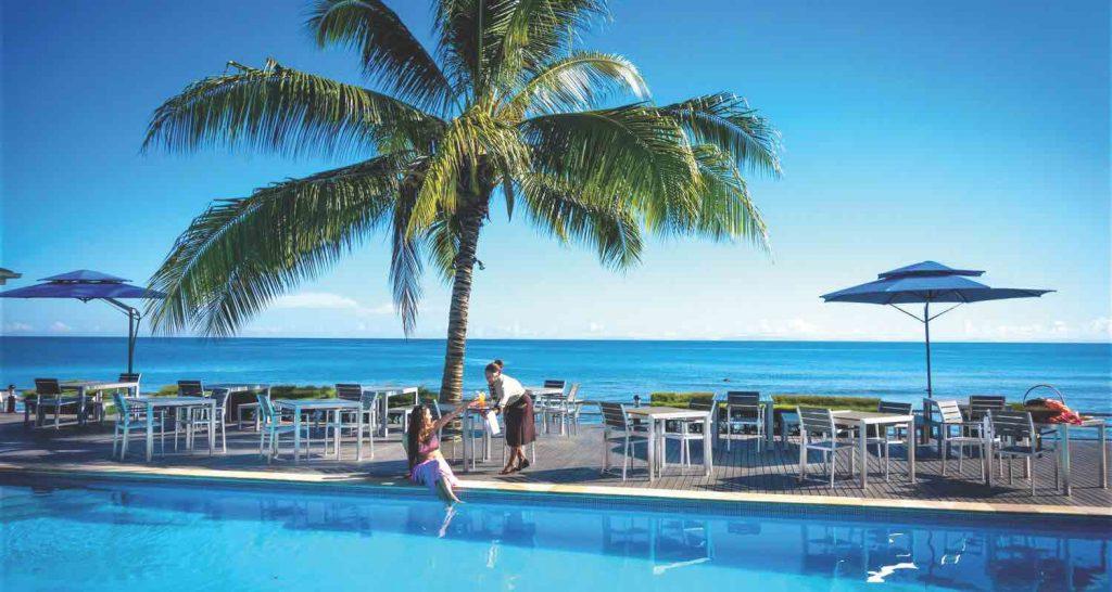 woman sitting by a hotel pool